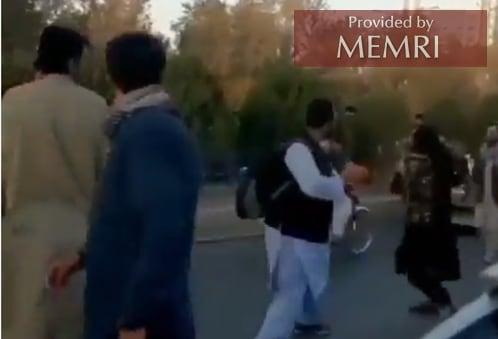 Un combatiente talibán, vestido de negro, golpea a un civil en la ciudad de Kabul